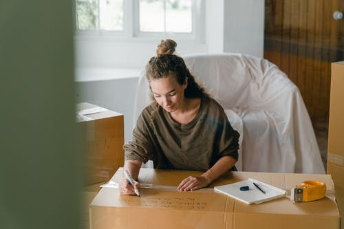 Woman signing box with marker while sitting in living room