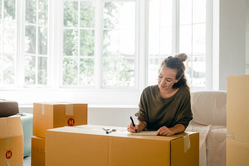 Content lady in casual clothes writing with pen on cardboard box while sitting near window in daylight in apartment preparing to relocate