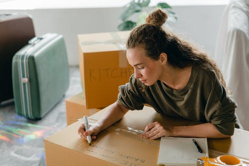 Top view of thoughtful lady in casual wear writing with marker on cardboard box while sitting near suitcases and pile of boxes in light living room