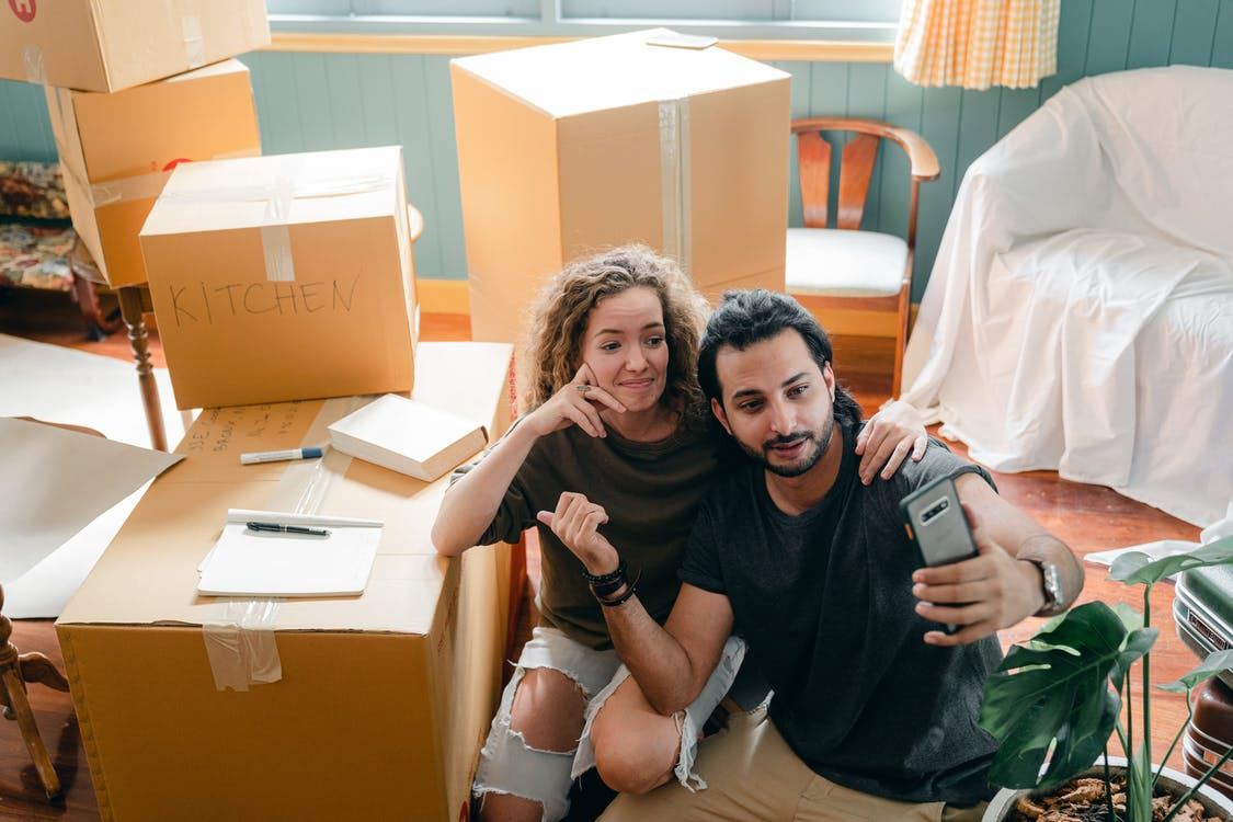 Top view of trendy woman embracing ethnic boyfriend in casual wear while taking selfie on cellphone and sitting surrounded by heap of cardboard boxes near sofa covered with bed sheet