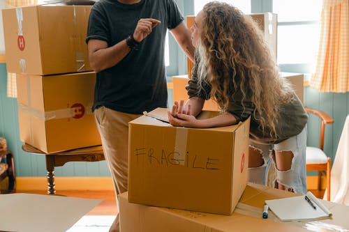 Woman and crop boyfriend near different boxes for moving