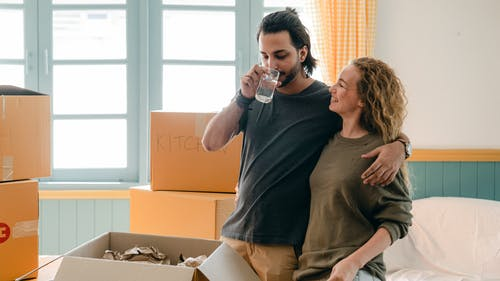 Cheerful multiethnic couple embracing while drinking water near different boxes