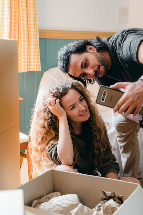 Multiracial couple taking selfie on smartphone while unpacking in new home