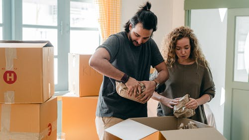 Diverse couple packing belongings in parchment near different boxes indoors