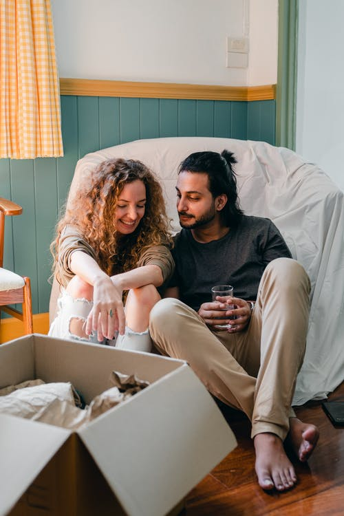 Positive multiethnic couple chatting while sitting in room and packing