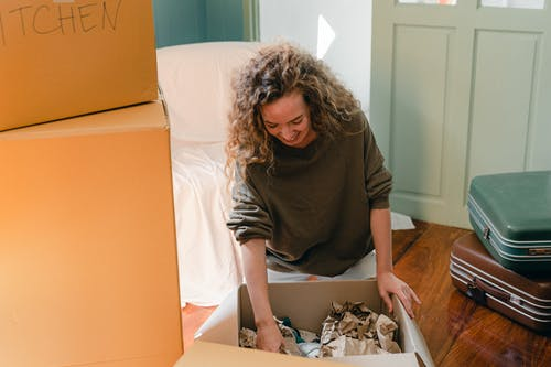 Happy woman unpacking carton box in living room