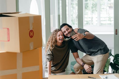 Positive laughing diverse couple in casual clothes taking selfie on smartphone and hugging while unpacking belongings in new cozy apartment