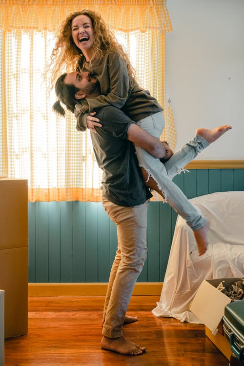 Side view full body barefoot happy bearded male in casual wear lifting cheerful laughing girlfriend up while unpacking belongings from carton boxes in new cozy apartment