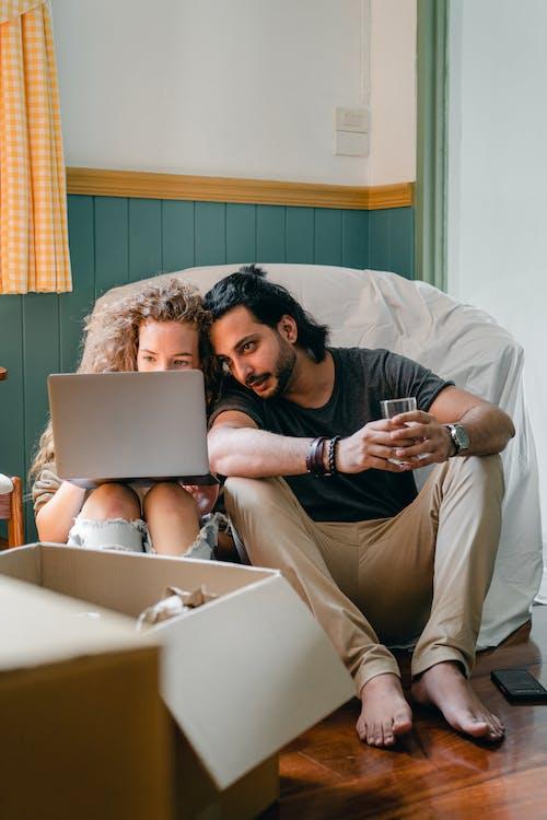 Positive couple using laptop near carton boxes