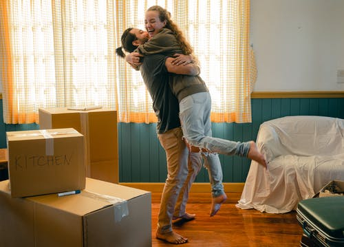 Side view full body barefoot young bearded male in casual clothes standing against window and lifting laughing girlfriend up during relocation and unpacking things from cardboard boxes
