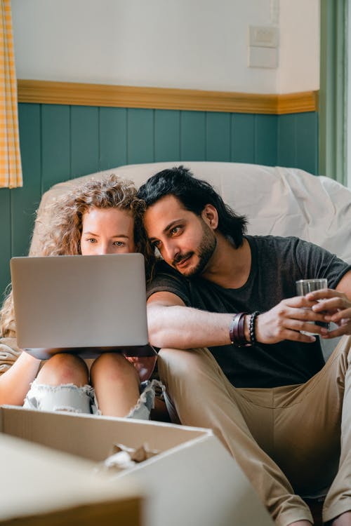 Content loving couple browsing laptop on floor