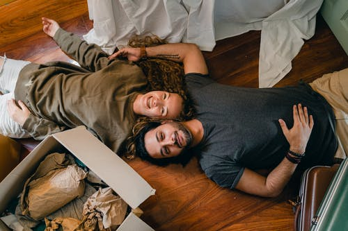 Cheerful couple lying on floor and laughing