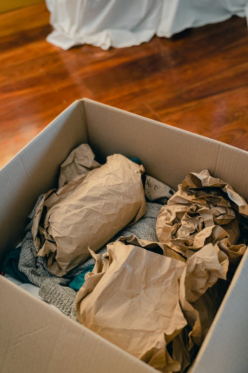 Box with objects wrapped in brown paper for moving