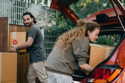 Positive multiethnic boyfriend and girlfriend unloading car trunk during moving to new home in quiet green yard on summer day