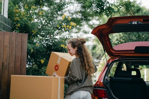 Young woman carrying box to new home while unpacking car