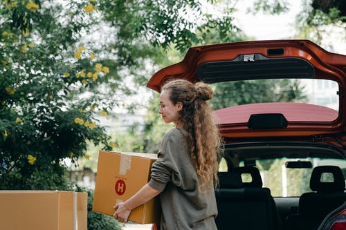 Positive young woman in casual sweatshirt taking cardboard boxes out of trunk compartment while moving into new home with blossoming garden