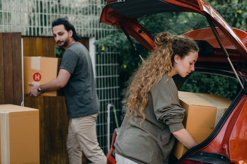 Young couple unpacking car in yard of new house