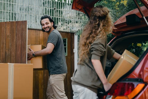 Cheerful modern male and female in comfortable casual clothes unpacking car trunk in green garden of new house while moving in together