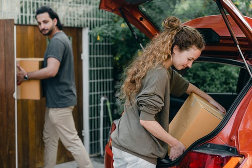 Modern couple unpacking car while moving to new place