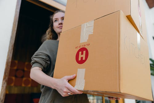 Young female carrying cardboard boxes while moving out of house