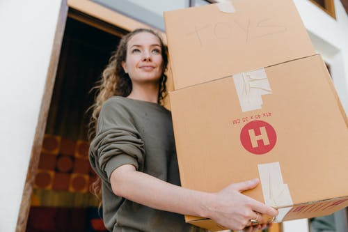 Young woman with boxes while moving out of old home
