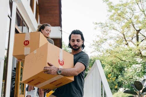 Young multiracial boyfriend and girlfriend in casual wear carrying big carton boxes and watching step on porch stairs while moving out of old home on sunny day in summer