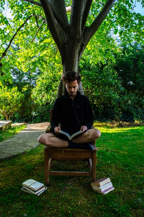 A Man Sitting on Wooden Chair while Reading a Book