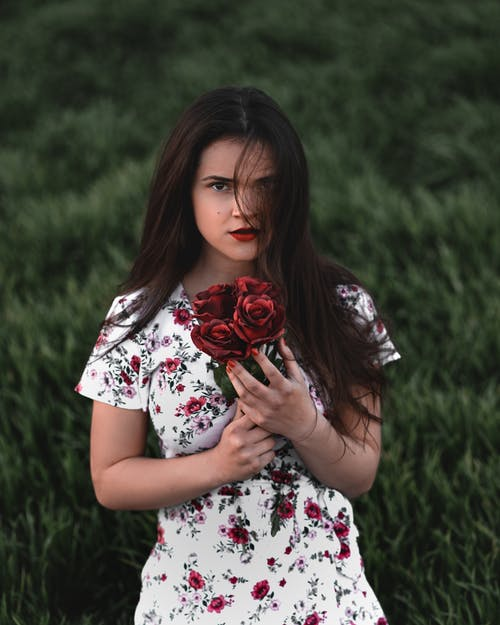 Woman in Floral Top Holding Red Roses while Looking at Camera