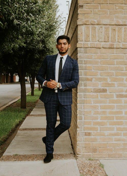 Smiling ethnic gentleman in elegant suit standing near old wall
