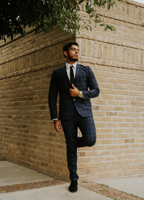Full body of contemplative ethnic male in stylish outfit leaning with leg on old shabby brick wall under tree on city street and looking away