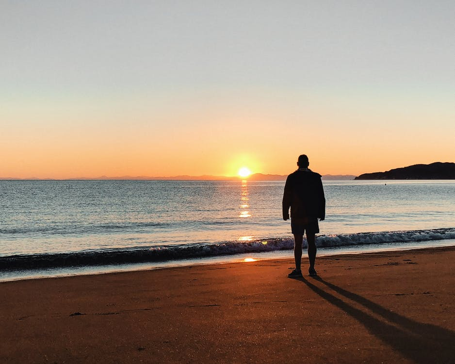 Silhouette of Man Standing on Beach during Sunrise