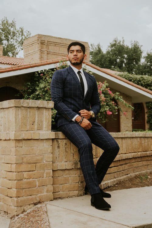 Handsome ethnic man in formal suit sitting on brick fence