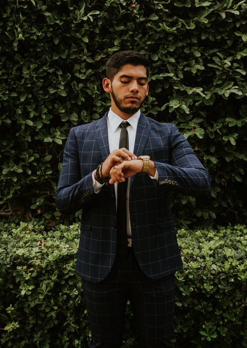 Serious ethnic brunet in formal wear with tie looking at wristwatch while standing behind shrubs in daylight