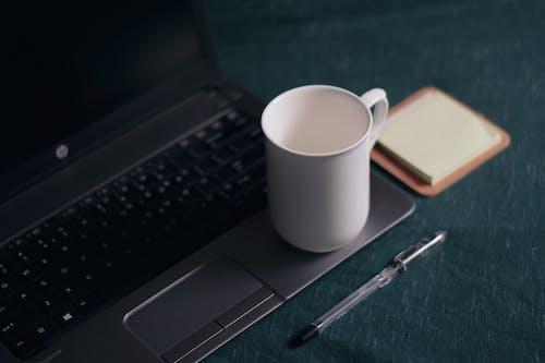 Mug on modern laptop near notepad stickers on table