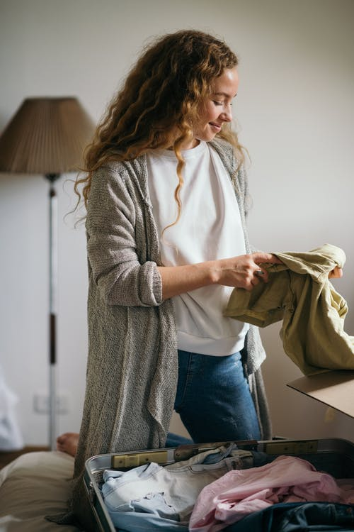 Cheerful young female packing suitcase in bedroom while moving house