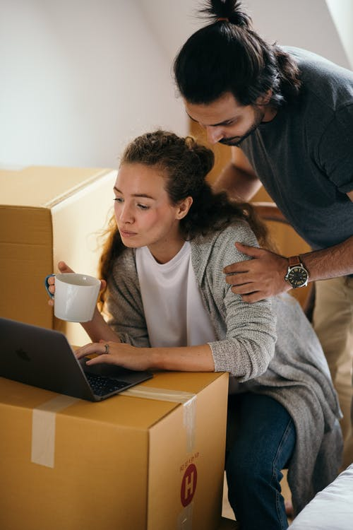 Young couple using laptop in room full of packed boxes