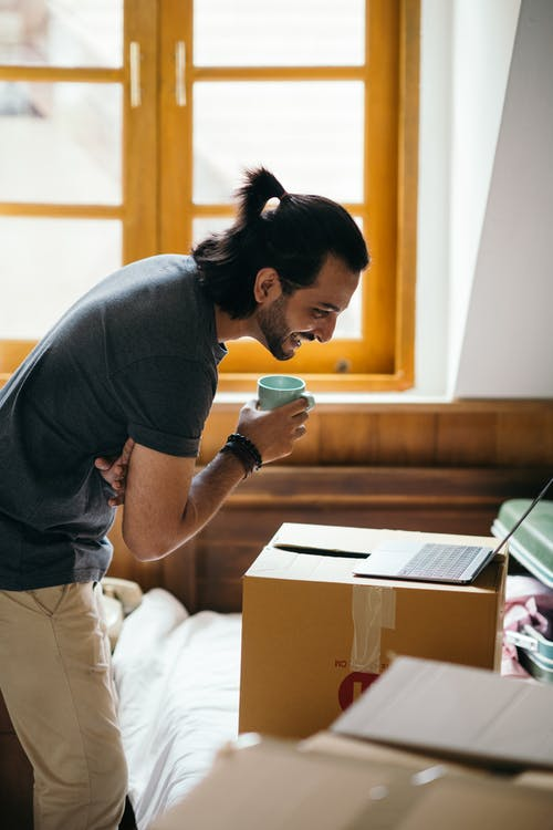Side view of happy young ethnic brunet with cup of coffee leaning forward and looking at screen of laptop placed on top of packed carton boxes on bed