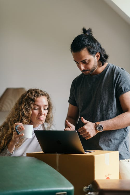 Young couple buying things for new house online using laptop - what to look for when buying a house.