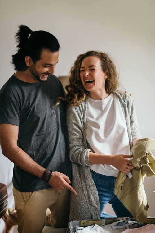 Young multiracial man and woman laughing happily at contents of travel suitcase in bedroom while packing clothes for journey