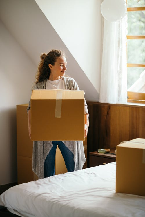 Young smiling lady in casual outfit with big cardboard box in hands standing and looking away near bed in modern bedroom of newly purchased house