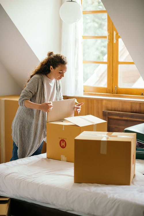 Serious female with curly hair carefully packing stuff in boxes preparing for moving out light apartment