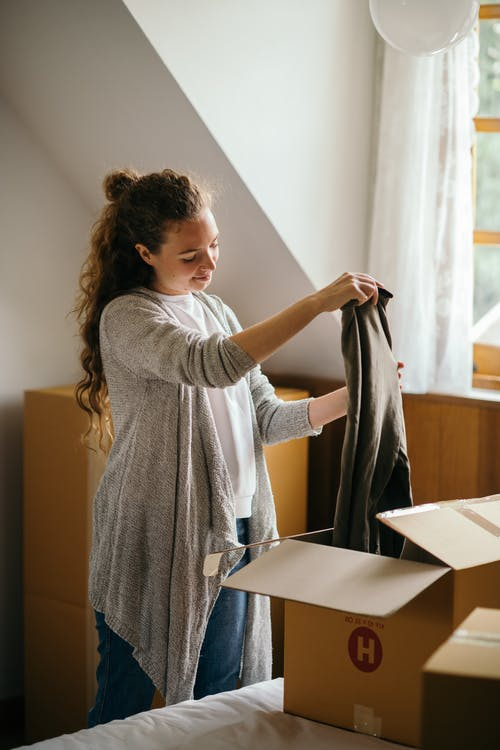 Peaceful woman carefully packing carton boxes