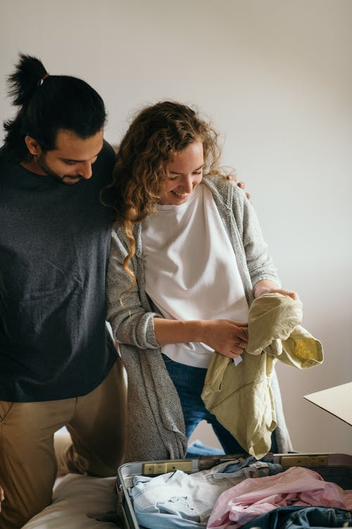 Happy couple packing baggage together in bedroom