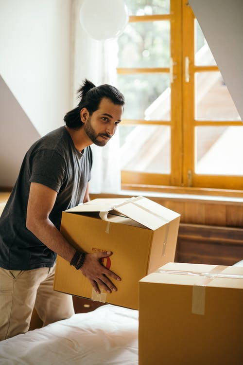 Thoughtful ethnic man holding cardboard box preparing to relocate