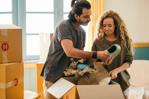 Pensive multiracial couple unpacking vase after renting new apartment