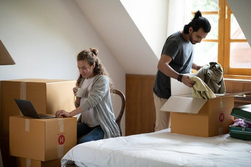 Woman typing on laptop while ethnic boyfriend unpacking clothes
