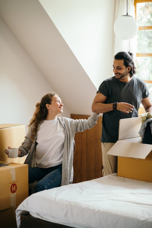 Happy couple unpacking boxes in new apartment