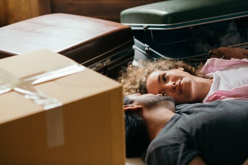 From above of man and woman looking at each other while lying on floor during preparing for relocation among carton boxes and suitcases