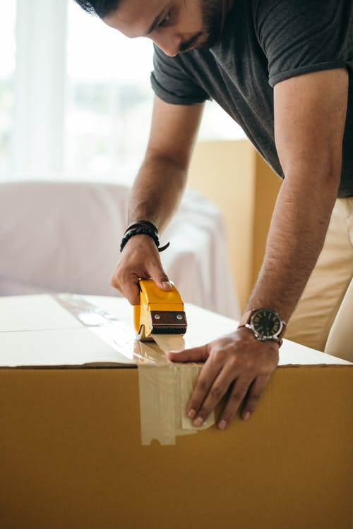 Side view of concentrated crop ethnic male sticking cardboard box with tape during preparing for moving in house at daytime