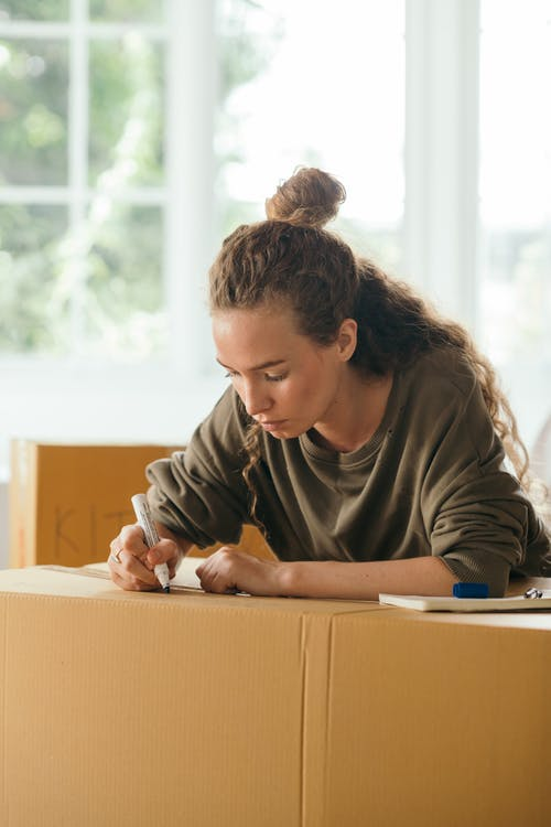 Focused woman signing boxes with packed stuff